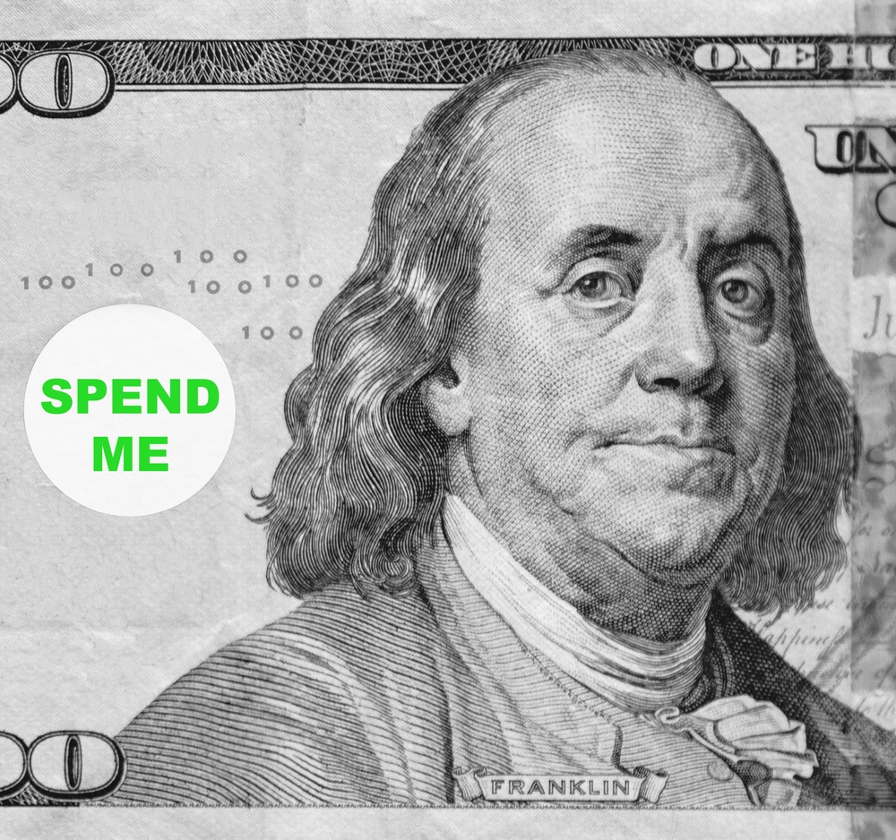 "Macro portrait of Benjamin Franklin from hundred-dollar U.S. bill with word balloon ""Spend me"" (in black and white, except for green text; some identifiers have been removed)"