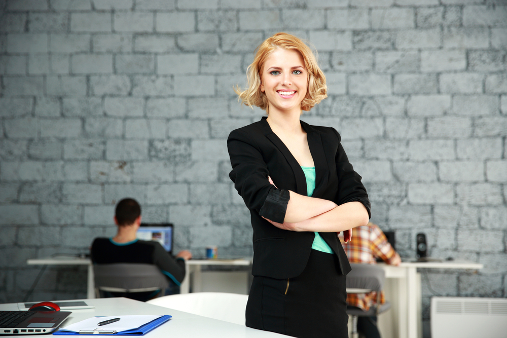 Young happy businesswoman with arms folded standing in office