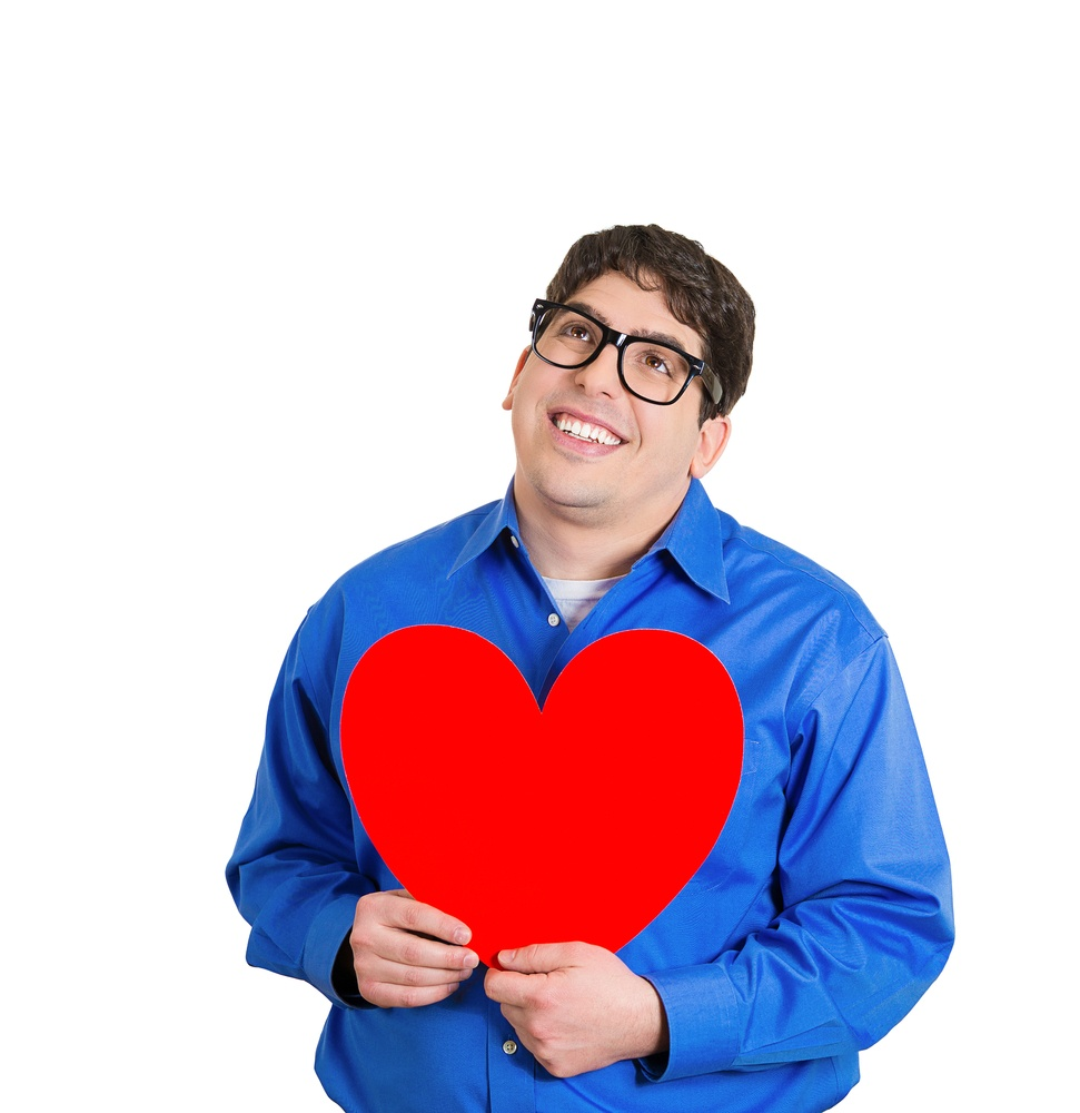 Closeup portrait of happy smiling handsome funny looking man, holding large red heart to chest daydreaming of women in love, isolated on white background. Positive emotions, facial expression feelings